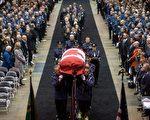 圖:Davidson的靈柩覆蓋著國旗,由8名警員扶靈進入會場,緊隨其後的警員手持Davidson生前的警帽和制服。他的家人跟著靈柩進場。(加通社)