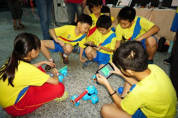 小朋友透过平板游戏,学习输入指令,驱动机器人,在对战游戏中,学会程式语言与设计。(李怡欣/大纪元)