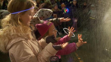 冰雕師傅正在拿著電鑽,打磨造型,邊上觀看的小孩子,被噴灑而來的冰屑逗得相當開心。