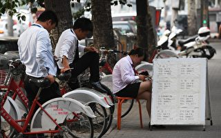 北京二手房市場持續低迷,近期現全面「砍價」行情。圖為北京街頭的地產經紀。(GREG BAKER/AFP/Getty Images)