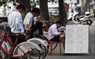 """今年北京市新房和二手房成交量双双""""腰斩""""。图为北京街头的房地产中介。(GREG BAKER/AFP/Getty Images)"""