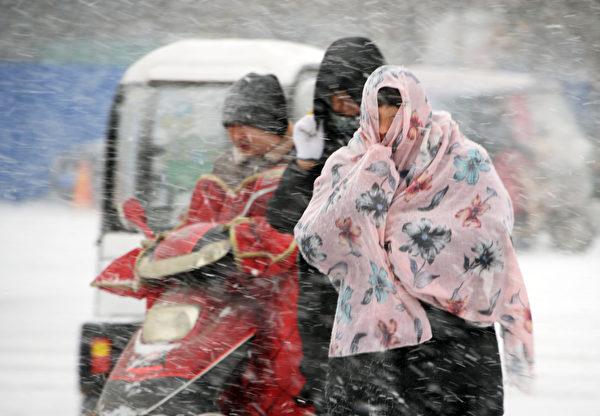 近日,江苏、浙江、上海等8省市下大雪,局地暴雪。图为雪中的南通居民。(AFP/Getty Images)