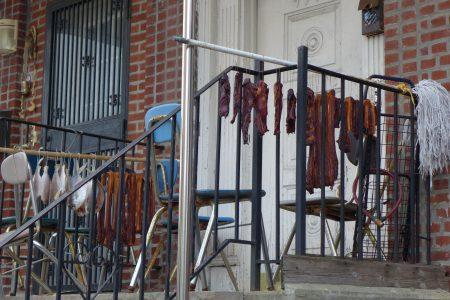 布碌崙九大道一户民宅内的华人家庭在前院晾晒腊肉和风干鱼。