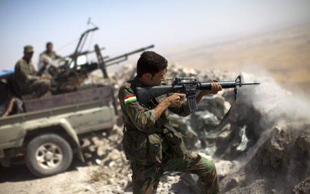 学者表示,川普板起脸去修理的都是邪恶对象,例如IS、北韩和墨西哥。图为伊拉克战士向IS武装阵地射击。