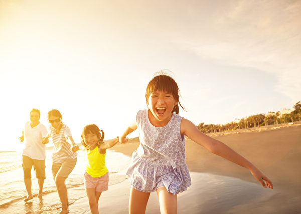happy family running on the beach.(shutterstock)