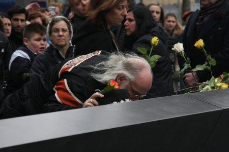 老人亲吻遇难者的名字。