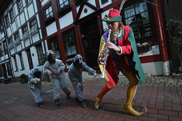 2012年11月19日,哈默爾恩市的旅遊局職員裝扮成花衣吹笛人,帶領扮作老鼠的孩子在市內走過。(Sean Gallup/Getty Images)