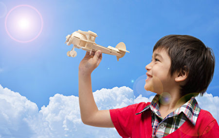 小男孩玩飞机木制玩具,蓝天