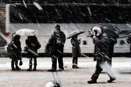在通勤早高峰,雨雪交加導致路面濕滑,民眾打著雨傘在風雪中等車。