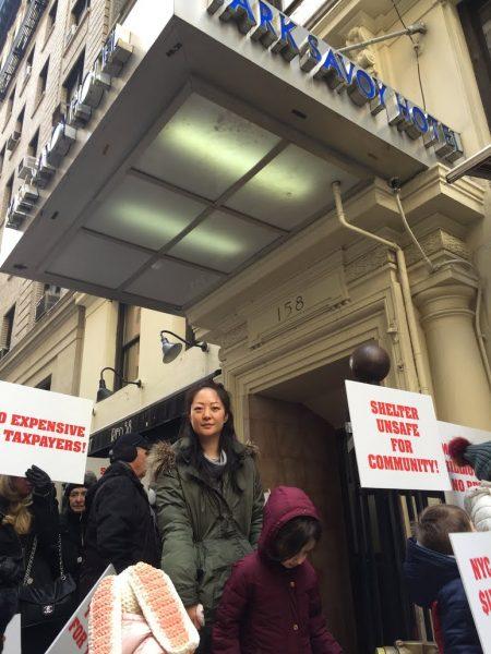 中央公园韩裔店主金女士带女儿在萨沃伊公园酒店前抗议游民收容所改建计划。