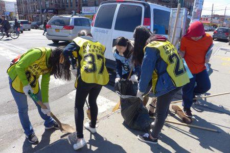 學生們拿著掃把分組,在八大道清掃沿街的垃圾。