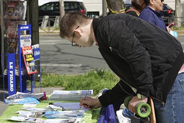 法國紀念法輪功學員四·二五萬人和平上訪19週年的集會上,過往民眾紛紛簽名聲援法輪功反迫害。(關宇寧/大紀元)