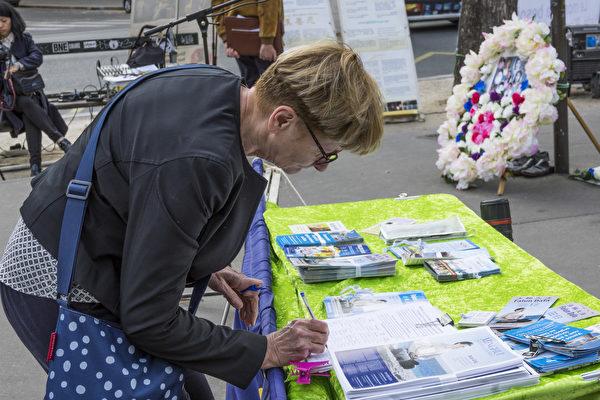 法国纪念法轮功学员四·二五万人和平上访19周年的集会上,过往民众纷纷签名声援法轮功反迫害。(关宇宁/大纪元)