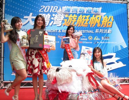 台湾小姐展示大鹏湾观光产业在地联盟特色商品与创意环保船合影。