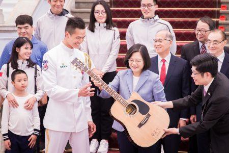 總統蔡英文(前右2)10日在總統府接見海軍儀隊隊員蘇祈麟(前右3)與其家屬,並送一把親筆簽名的吉他給蘇祈麟。