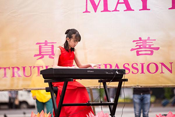 2018年5月10日,纽约部分法轮功学员在联合广场集体炼功,庆祝法轮大法日。Duo Duo表演钢琴独奏《走在神的路上》(戴兵/大纪元)