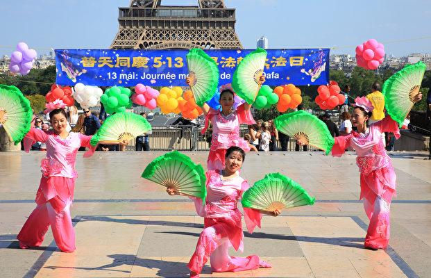 2018年5月20日在法国巴黎铁塔对面的人权广场上,法国部分法轮功学员用歌舞演出和功法演示庆祝第十九届世界法轮大法日。(章乐/大纪元)