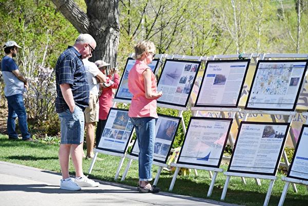 2018年5月13日世界法輪大法日,部分卡爾加里法輪功學員在王子島公園舉行慶祝活動。圖為路人駐足觀看真相展板。(大紀元)