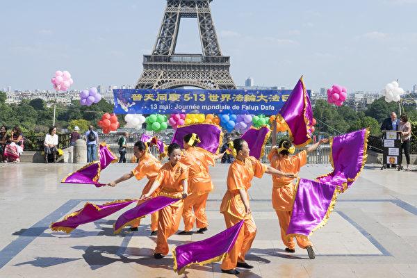 2018年5月20日在法国巴黎铁塔对面的人权广场上,法国部分法轮功学员用歌舞演出和功法演示庆祝第十九届世界法轮大法日。(叶萧斌/大纪元)