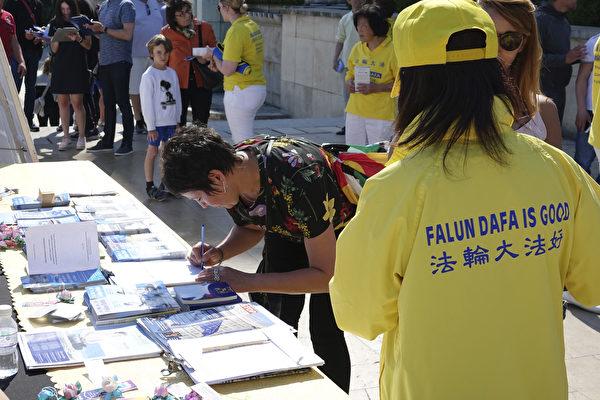 法国庆祝第十九届世界法轮大法日的活动上,过往民众纷纷在签名簿上留言签名,声援尽快结束这场史无前例的迫害,谴责中共的罪行。(叶萧斌/大纪元)