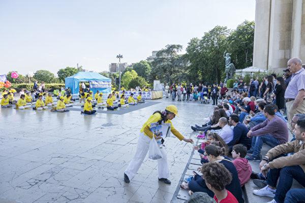 法国庆祝第十九届世界法轮大法日的活动上,很多过往民众兴高采烈地观看法轮功学员的歌舞节目和功法展示,不停地拍照留念。(叶萧斌/大纪元)