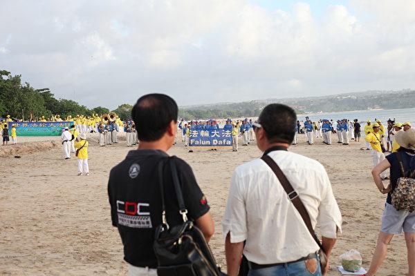峇里島法輪功學員在金巴蘭海灘慶祝世界法輪大法日。中國遊客駐足觀看。(Ketut Suyasa提供)
