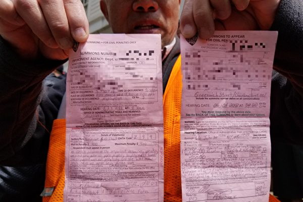 刘先生在集会现场气愤地出示他收到的罚单。3~4月间,不到12天时间,就吃了两张罚单,罚款共一千美元。(玉凌格/大纪元)