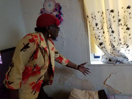 市议员巴伦指著布勒克伦公屋东105街716号6D公寓的一间房间墙壁,说明油漆剥落情形,并说房间空气不佳。