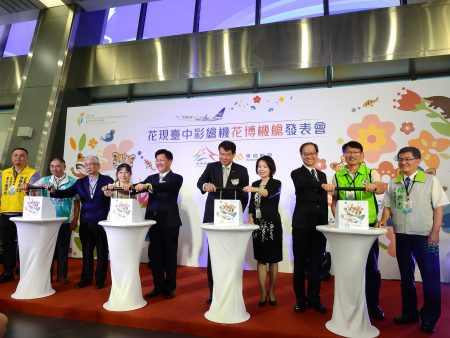 """林佳龙市长(左5)、何煖轩董事长(左6)与贵宾共同主持""""花现台中彩绘机-花博机舱""""发表会。"""