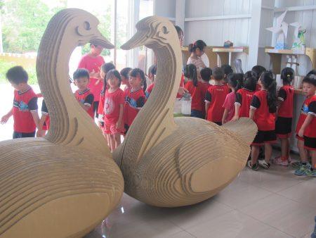 幼儿园的小朋友挤着看大哥哥大姊姊的作品。