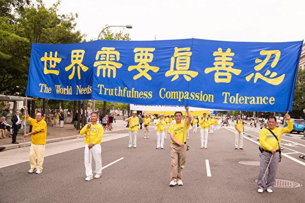 """6月20日,全球部分法轮功学员聚集在美国首府华盛顿DC,举行反迫害集会游行。图为游行队伍中的""""世界需要真善忍""""大型横幅。(戴兵/大纪元)"""
