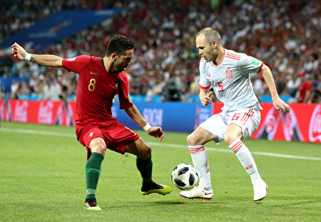 SOCHI, RUSSIA - JUNE 15: Andres Iniesta of Spain challenge for the ball with Joao Moutinho of Portugal during the 2018 FIFA World Cup Russia group B match between Portugal and Spain at Fisht Stadium on June 15, 2018 in Sochi, Russia.