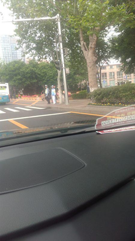 路口的警察與戴有袖標的人員。(知情人提供)