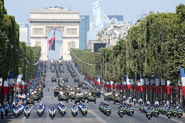 Members of the 'Escadron motocycliste de la police nationale' (front L), of the 'escadron motocycliste du centre national de formation a la securite routiere de la gendarmerie nationale (front R) and military vehicles take part in the annual Bastille Day military parade on the Champs-Elysees avenue near the Arc de Triomphe in Paris on July 14, 2018.