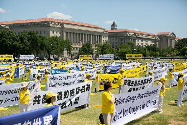 法輪功學員在集會現場手持橫幅,呼籲制止迫害。(李莎/大紀元)