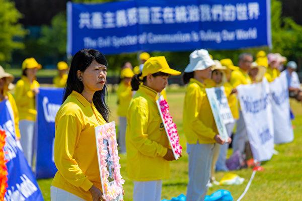 法輪功學員手持被迫害致死的同修照片,呼籲制止迫害。(Mark Zou/大紀元)