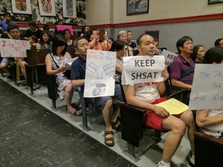 華人家長旁聽第26學區教育委員會會議,手持要求保留SHSAT的標語,表達呼聲。