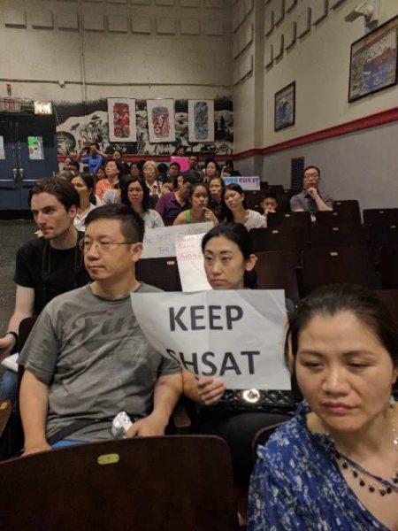 华人家长旁听第26学区教育委员会会议,手持要求保留SHSAT的标语,表达呼声。