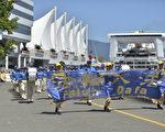 法輪功學員遊行隊伍途經溫哥華市中心著名旅遊景點,溫哥華的地標五帆酒店。(大宇/大紀元)