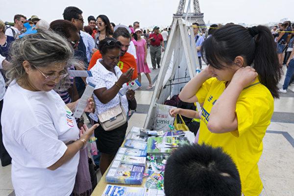 很多民眾開心地收到學員們製作的紙蓮花(葉蕭斌/大紀元)