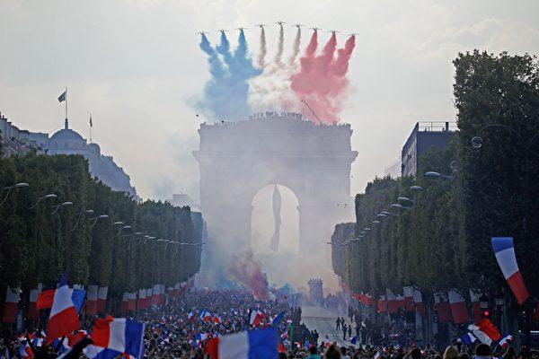 7月16日,法国巡逻兵飞行表演队(Patrouille de France)拖着喷洒出的蓝白红法国国旗三色烟雾为英雄凯旋的庆典助兴,场面分外壮观。(CHARLY TRIBALLEAU/AFP/Getty Images)