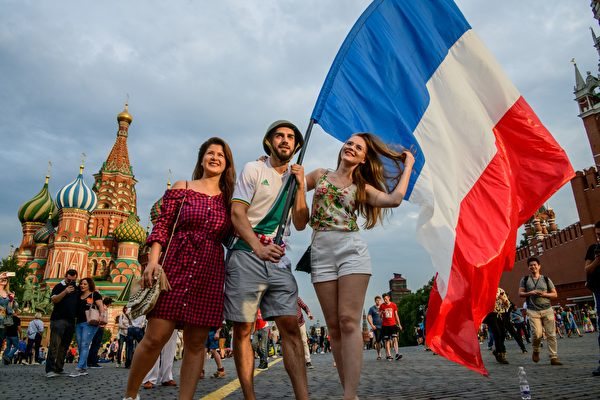 TOPSHOT - France fans hold a French flag as they pose at the Red Square in Moscow on July 14, 2018 on the eve of the Russia 2018 World Cup final football match between France and Croatia. (Photo by MLADEN ANTONOV / AFP)