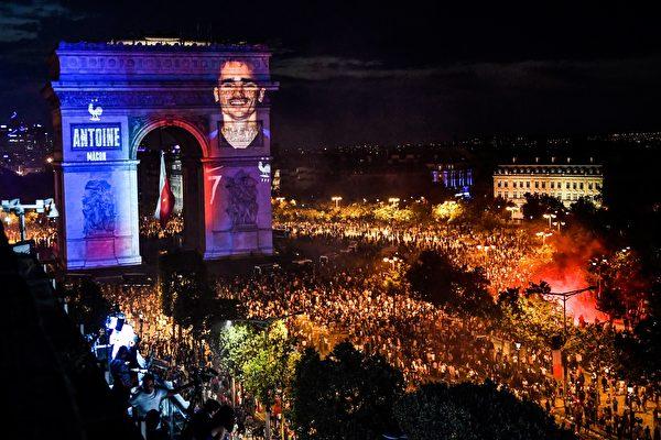 7月15日法国足球队力捧大力神杯,举国欢庆,夜里凯旋门穿上了蓝白红的灯光外衣,法国队队员们的照片也通过灯光投射在凯旋门上。(GERARD JULIEN/AFP/Getty Images)