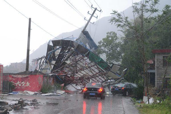 """2018年7月11日上午,今年第8号台风""""玛莉亚""""侵袭福州。图为福州市区一社区门前的一棵大树被台风刮断,将出行通道挡住。台风""""玛莉亚""""于当天09时10分在福建连江沿岸登陆。(大纪元资料室)"""