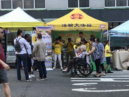 法轮功学员参加了街市节活动,展位跟前吸引各族裔的民众了解这个东方的中国古老文化——修炼。