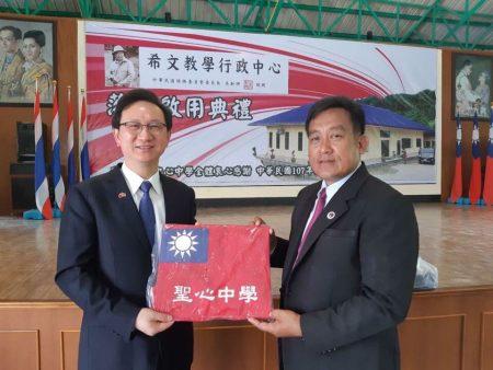 驻泰代表童振源(左)前往泰北华校探视,泰国清迈孟安圣心中学校长王绍章(左)致赠国旗书包。