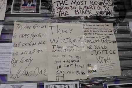 """非裔抗议民众在大门紧闭的""""红苹果""""美甲店闸门上表达不满,不达目的誓不罢休。"""