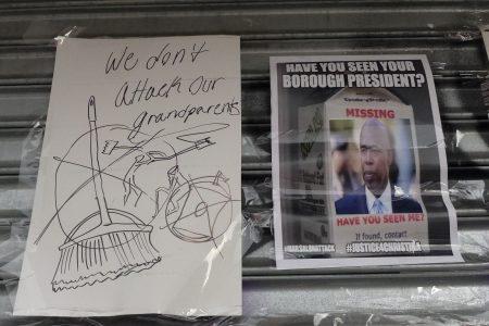 """非裔抗议民众在大门紧闭的""""红苹果""""美甲店闸门上表达不满,强调扫把杆打老奶奶""""绝不能接受""""。"""
