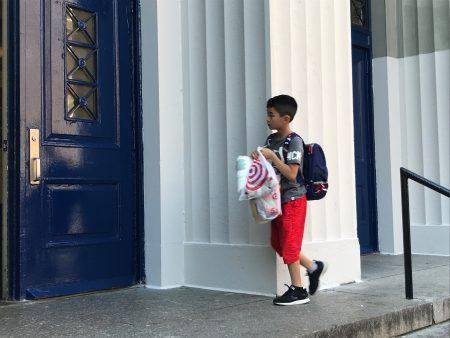 开学第一天,华人学生拧著学习用品进入学校。