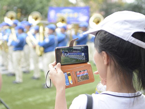 華人錄下天國樂團演奏的場景。(馬青/大紀元)